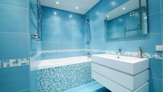 Salle de bain bleue avec des meubles blancs