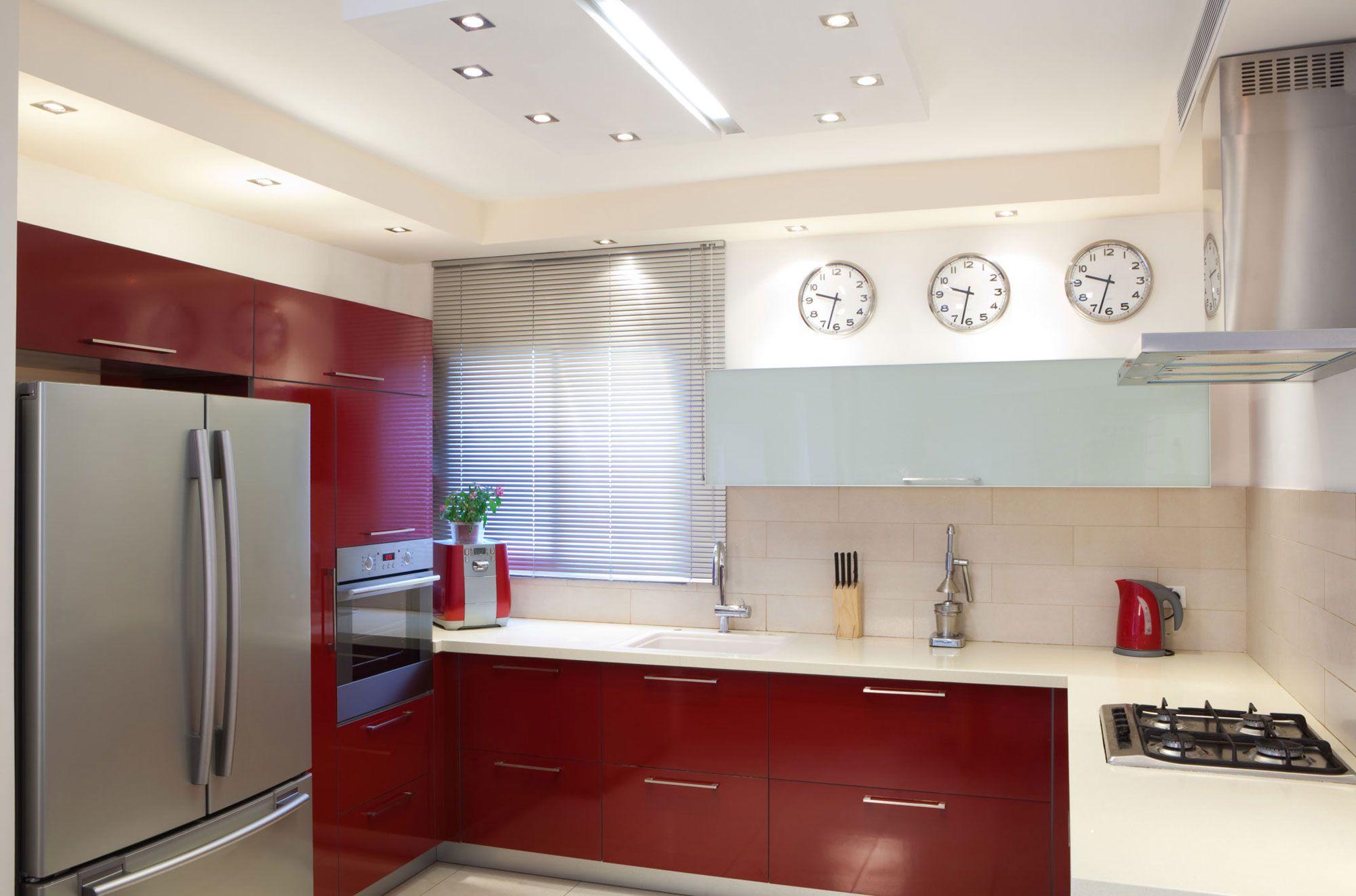 Cuisine blanche et rouge lumineuse ouverte sur le salon